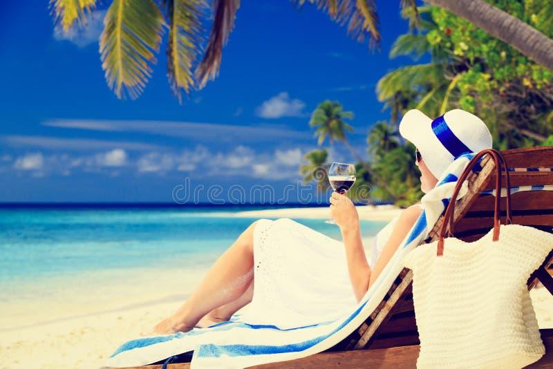 Kvinna som dricker vin på den tropiska stranden royaltyfria foton