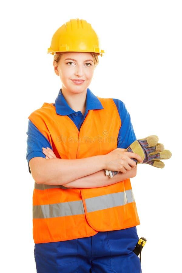 Kvinna som en byggnadsarbetare med hjälmen och säkerhetsvästen royaltyfri bild