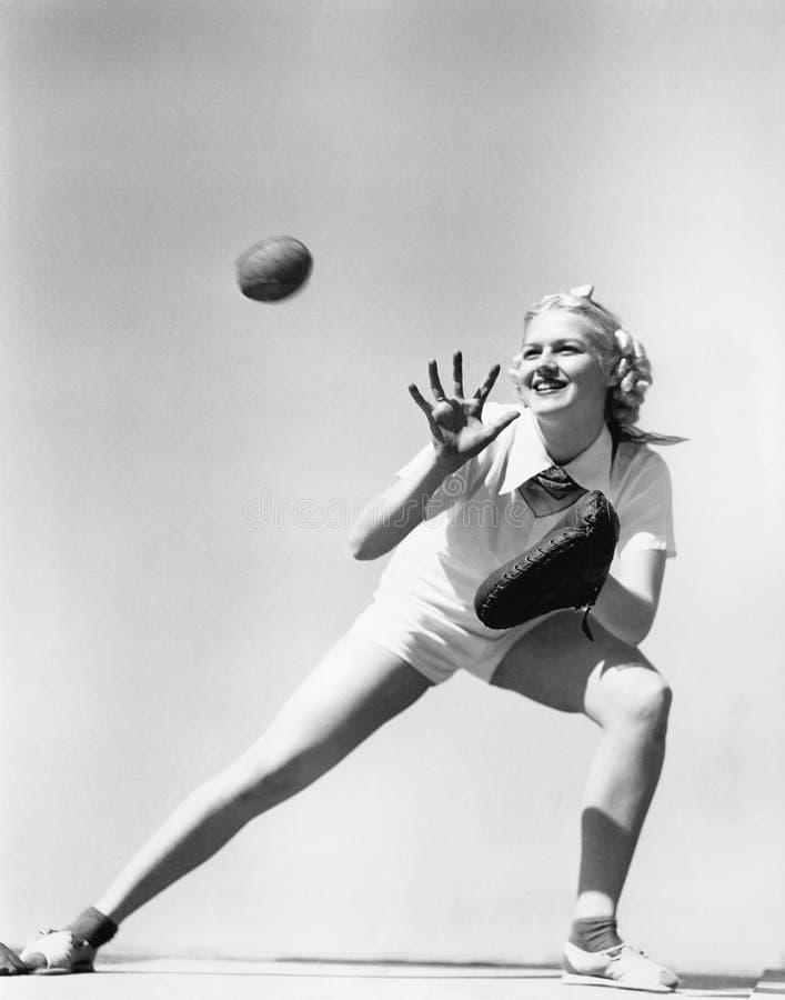Kvinna som fångar en baseball (alla visade personer inte är längre uppehälle, och inget gods finns Leverantörgarantier att det sk arkivbild