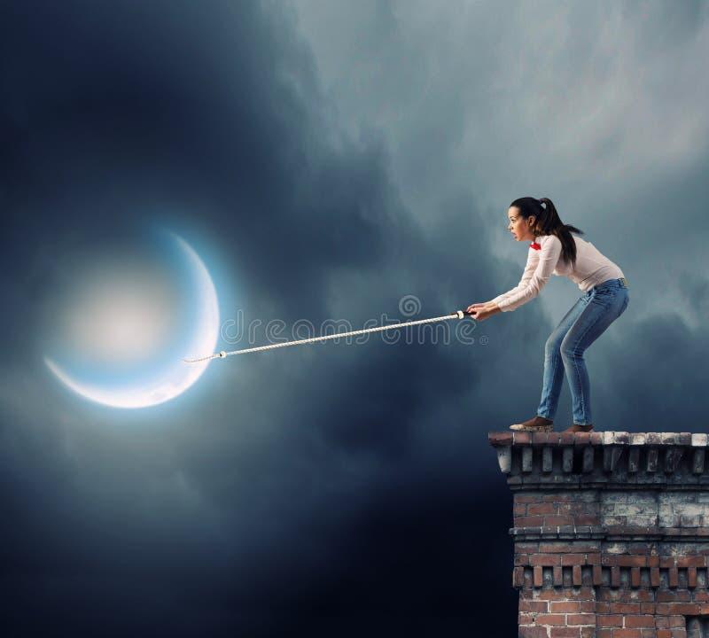 Kvinna som fångar månen royaltyfri foto