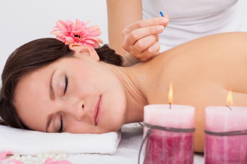 Kvinna som får akupunkturterapi royaltyfri foto
