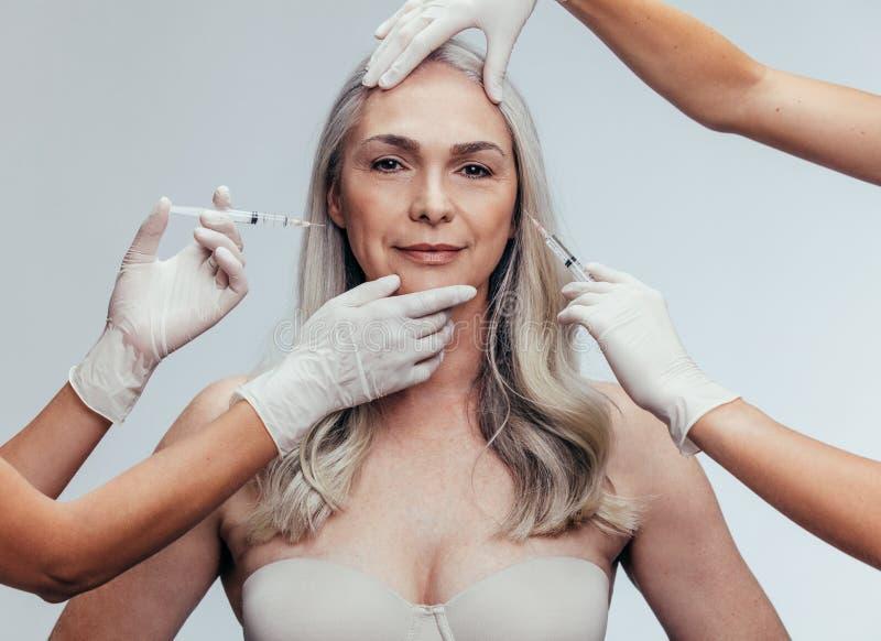 Kvinna som får anti-åldras kosmetiska injektioner arkivfoton