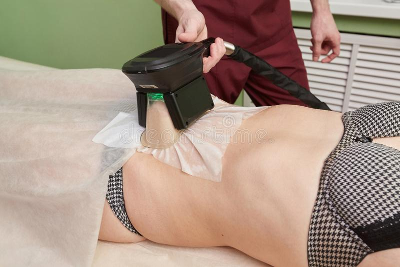 Kvinna som får cryolipolysis fet behandling i yrkesmässigt kosmetiskt kabinett royaltyfria bilder