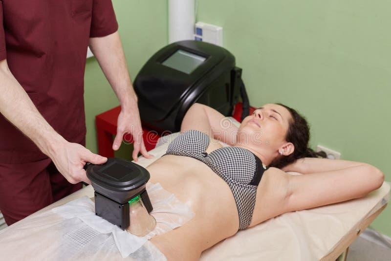 Kvinna som får cryolipolysis fet behandling i yrkesmässigt kosmetiskt kabinett royaltyfria foton