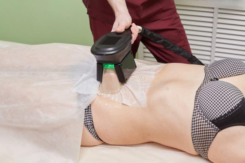 Kvinna som får cryolipolysis fet behandling i yrkesmässigt kosmetiskt kabinett arkivbilder
