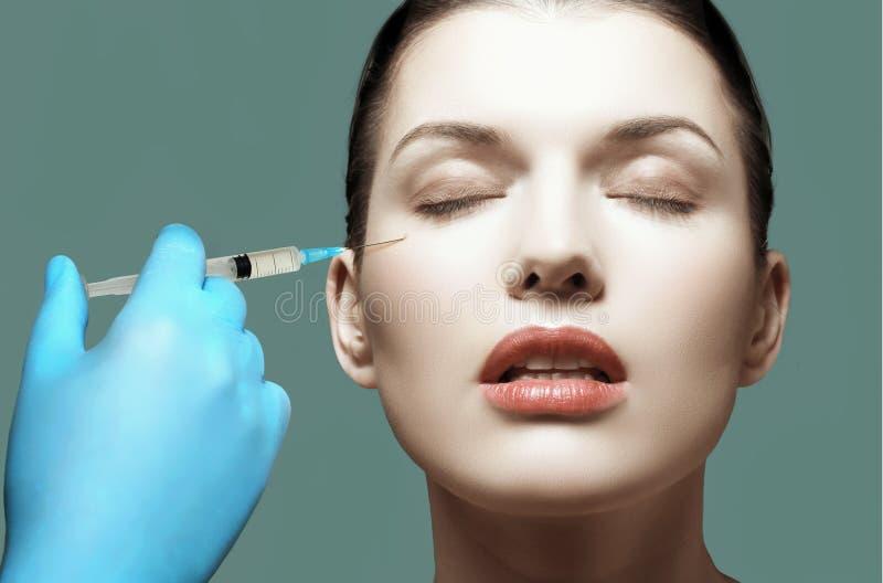 Kvinna som får den kosmetiska injektionen av botox i kinden, closeup royaltyfria bilder