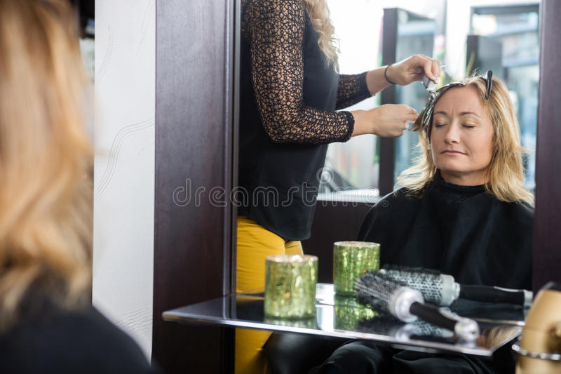 Kvinna som får den nya frisyren i mottagningsrum royaltyfri bild