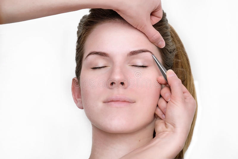 Kvinna som får det tweezing ögonbryn av beauticianen arkivbild