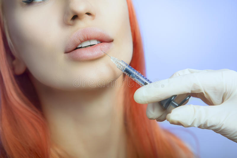 Kvinna som får en injektion i hennes kanter i skönhetsalong arkivfoton