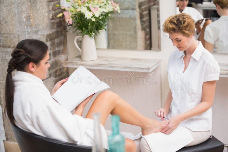 Kvinna som får en pedikyr från kosmetolog arkivbild
