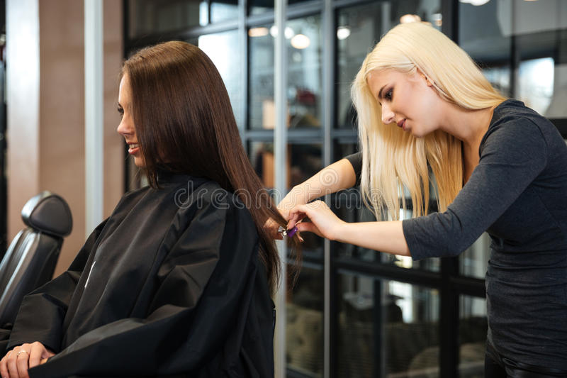 Kvinna som får frisyr av den kvinnliga frisören på skönhetsalongen arkivfoto