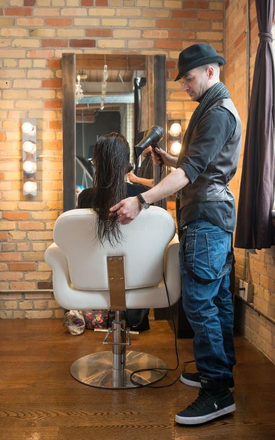 Kvinna som får hår utformat royaltyfri bild