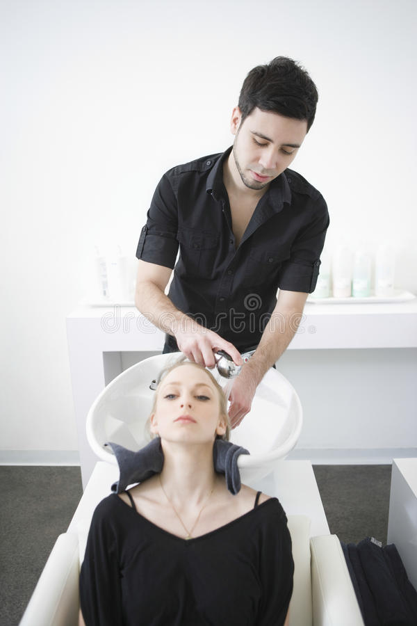 Kvinna som får hårWash från frisör i mottagningsrum royaltyfri fotografi