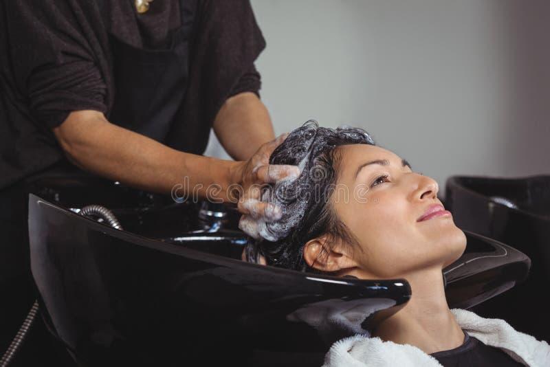 Kvinna som får henne hårwash royaltyfria bilder