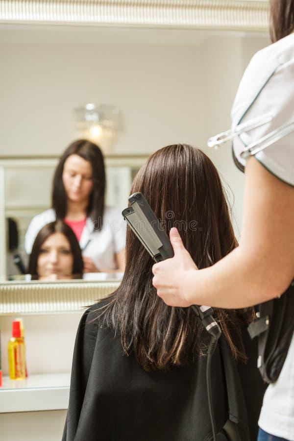 Kvinna som får hennes frisyr gjord på frisören arkivbild