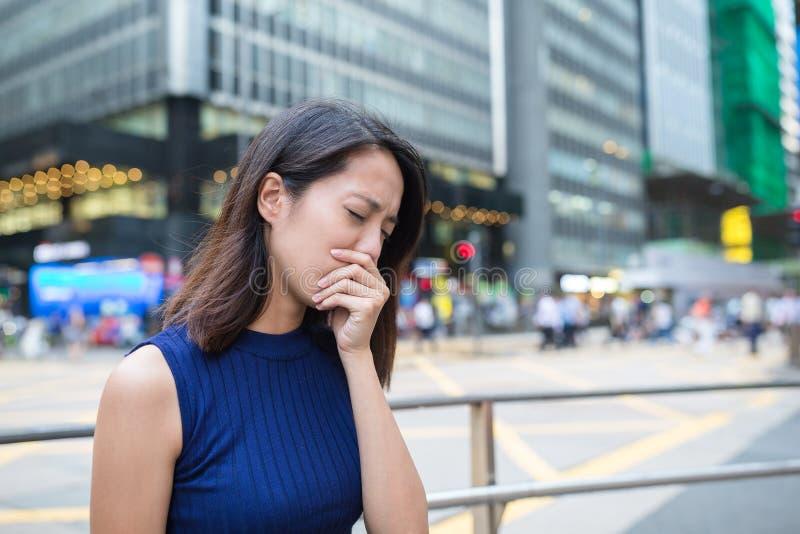 Kvinna som får sjuk på utomhus- arkivfoto
