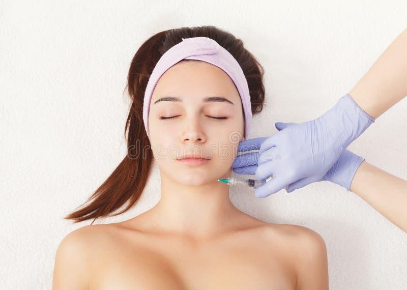 Kvinna som får skönhetinjektionen på salongen royaltyfri foto