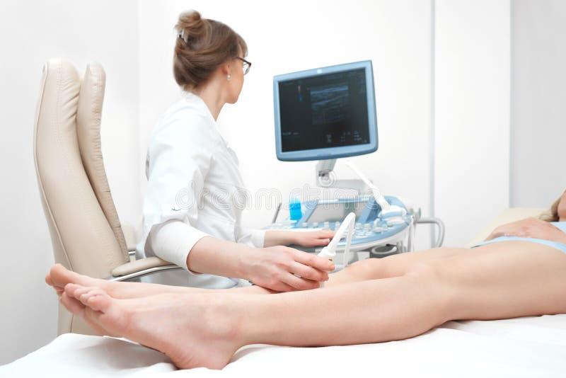 Kvinna som får undersökning för knäultraljudscanning på kliniken royaltyfri bild