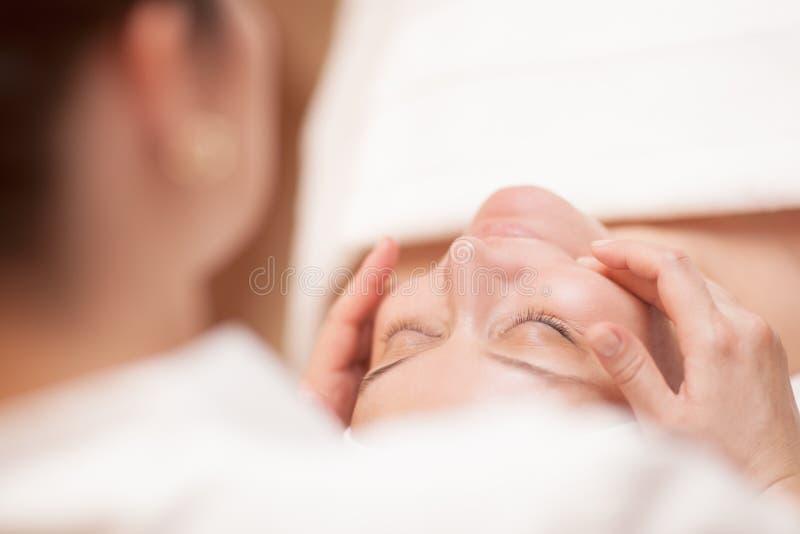 Kvinna som får yrkesmässig ansikts- massage arkivbild