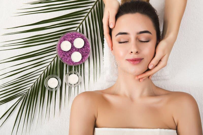 Kvinna som får yrkesmässig ansikts- massage på brunnsortsalongen royaltyfria foton