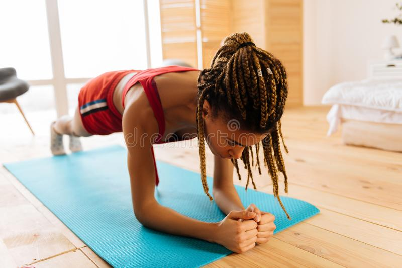 Kvinna som förbättrar uthållighet, medan stå i planka i morgonen arkivbilder