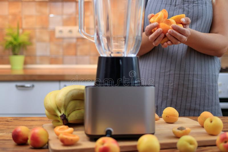 Kvinna som förbereder aprikossmoothien eller fruktsaft med frukter i köket arkivbild
