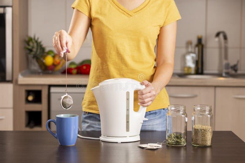 Kvinna som förbereder en kopp te arkivfoton