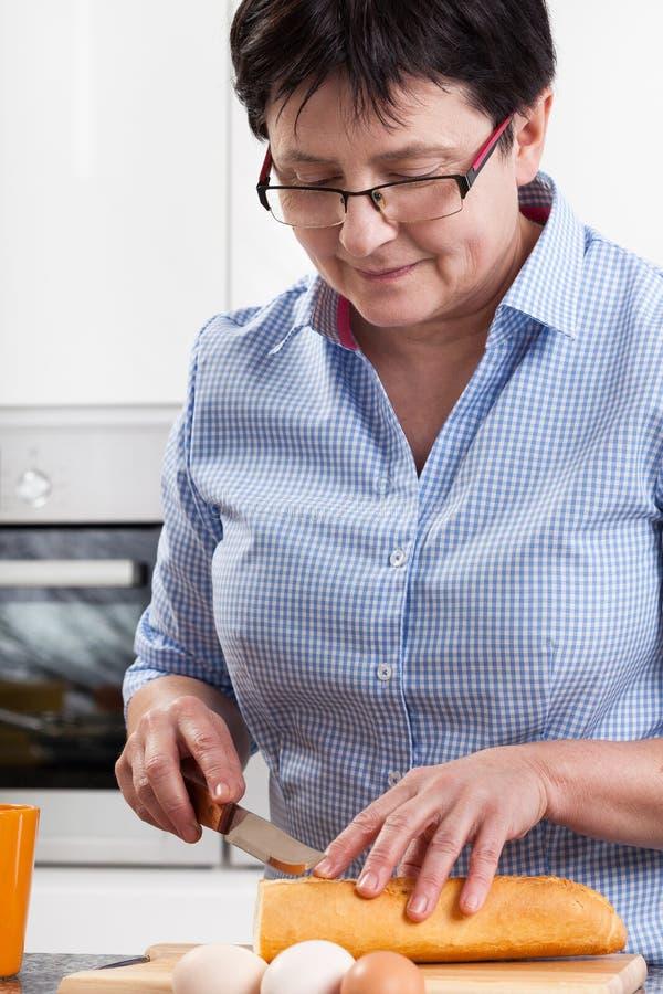Kvinna som förbereder frukosten arkivfoton