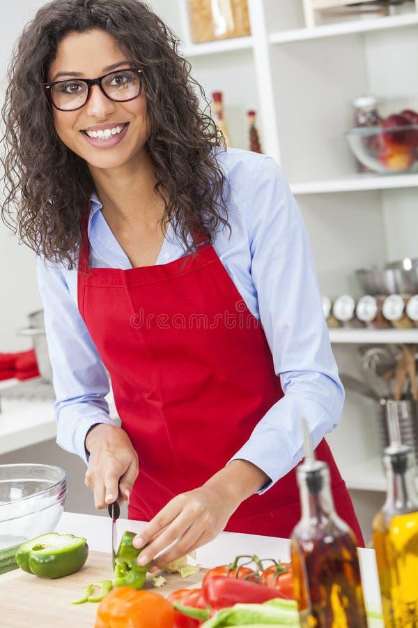 Kvinna som förbereder grönsaksalladmat i kök arkivfoto