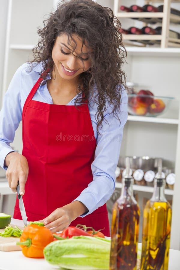 Kvinna som förbereder grönsaksalladmat i kök royaltyfria bilder