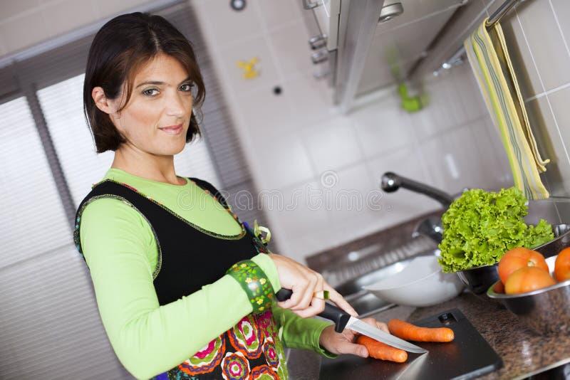 Kvinna som förbereder mat på köket royaltyfri bild