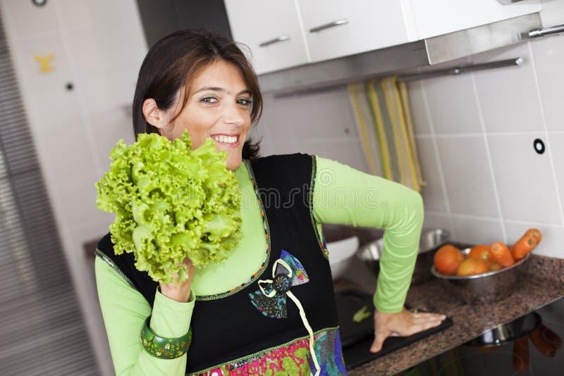 Kvinna som förbereder mat på köket arkivbilder
