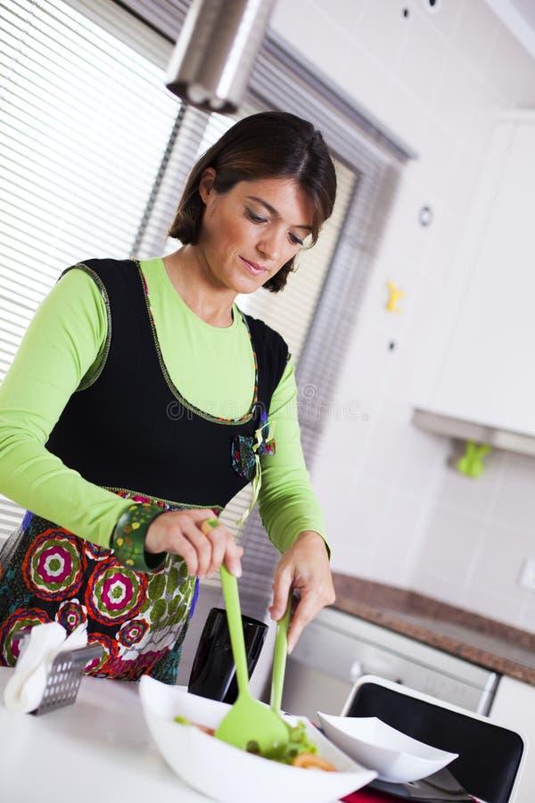Kvinna som förbereder mat på köket royaltyfria foton