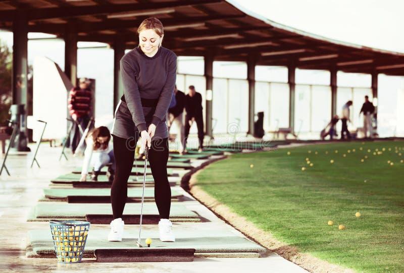 Kvinna som förbereder sig att slå bollen på golfbanan fotografering för bildbyråer