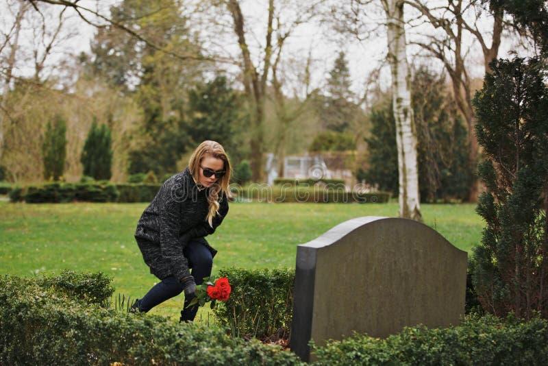 Kvinna som förlägger blommor på gravstenen i kyrkogård arkivfoto
