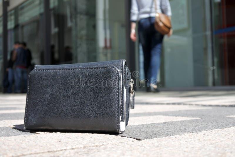 Kvinna som förlorar hennes plånbok på stadsgatan arkivbild