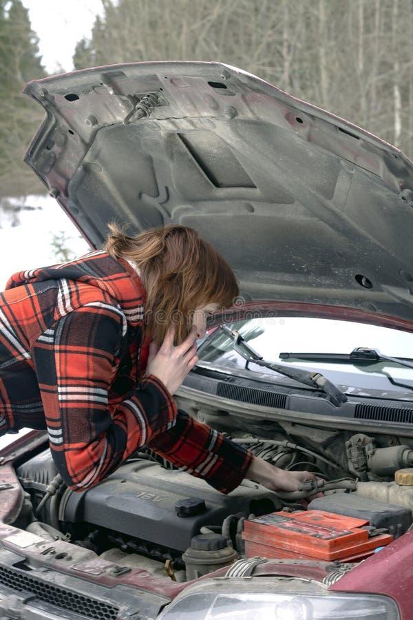 Kvinna som försöker att fixa den lyssnande rådgivningen för bil på telefonen royaltyfri fotografi