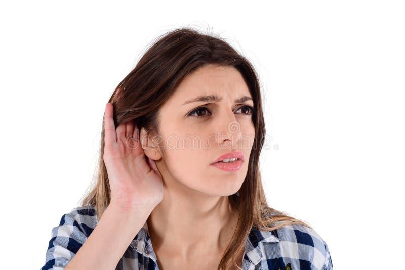 Kvinna som försöker att lyssna något royaltyfria bilder