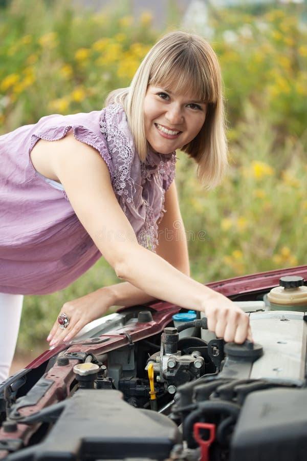 Kvinna som försöker att reparation bilen arkivfoton