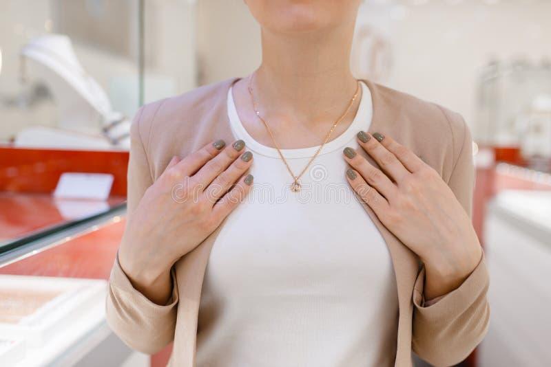 Kvinna som försöker på den guld- halsbandet i smyckenlager arkivbilder