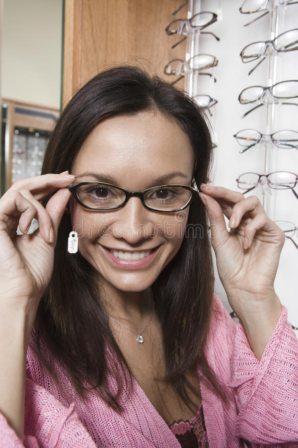 Kvinna som försöker på glasögon i lager royaltyfri bild