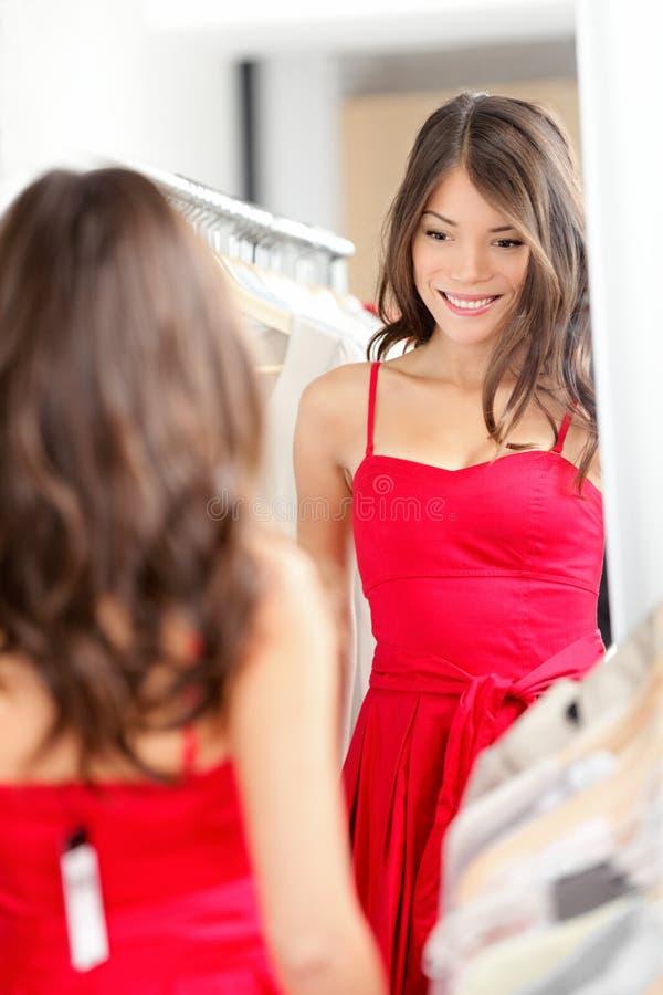 Kvinna som försöker på klänningen royaltyfri foto