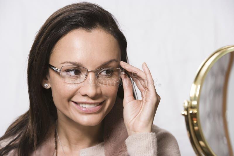Kvinna som försöker på nya exponeringsglas royaltyfria bilder