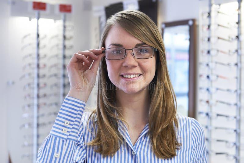 Kvinna som försöker på nya exponeringsglas i optiker arkivbilder