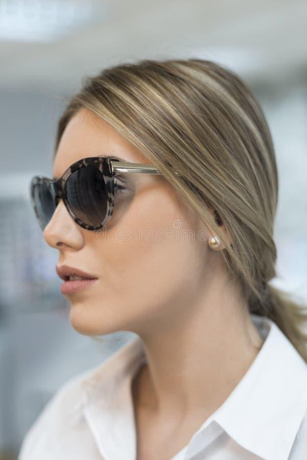 Kvinna som försöker på solglasögon i optiskt glasögonlager royaltyfri foto