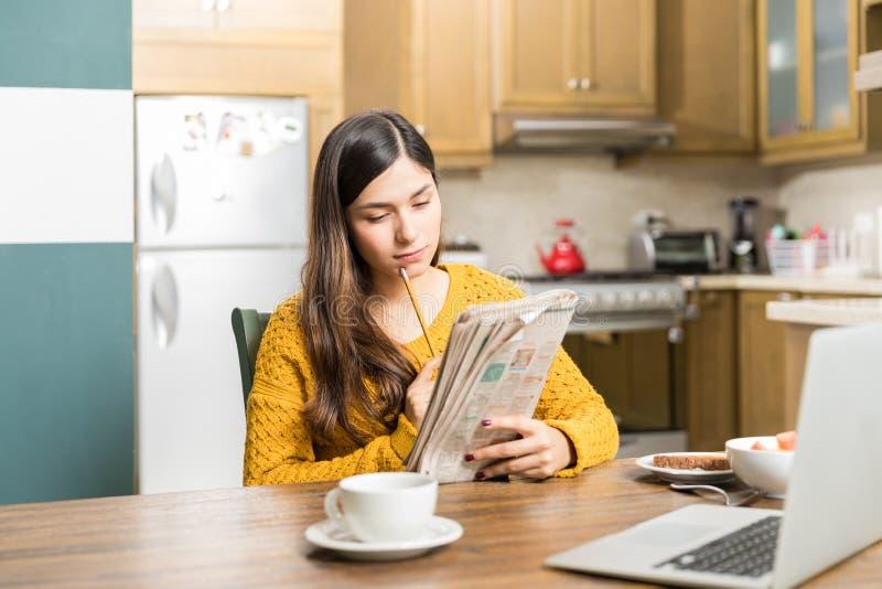 Kvinna som försiktigt analyserar tidningsleken arkivbild