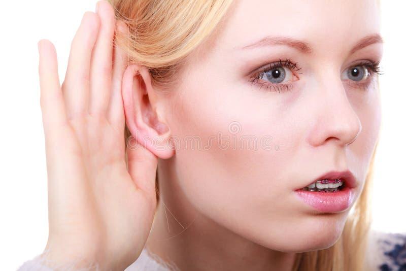 Kvinna som försiktigt nästan lyssnar med örat för hand royaltyfria bilder
