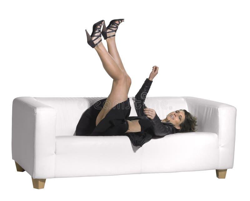 Kvinna som faller på soffan arkivfoto