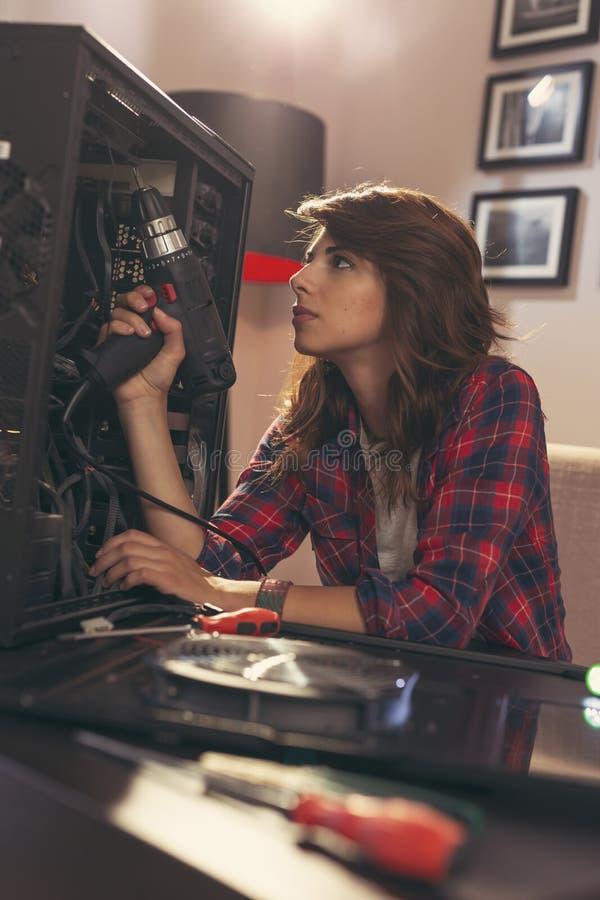 Kvinna som fixar en dator royaltyfri foto