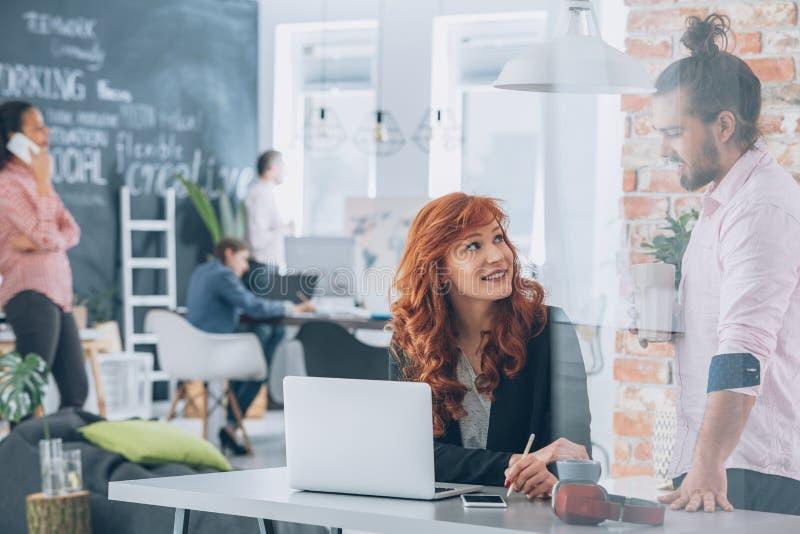 Kvinna som flörtar med coworkeren arkivbilder
